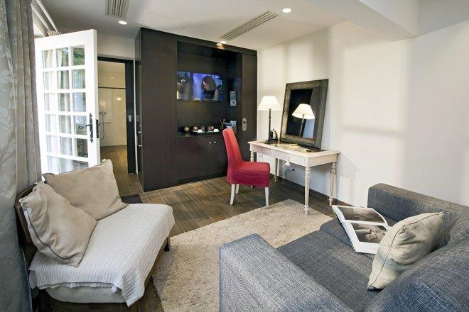 Chambre Lodge framboise avec espace bureau et canapé lit. décoration et détente dans un cadre idyllique pour un séjour ou un weekend en amoureux au domaine de Bellevue près de Paris