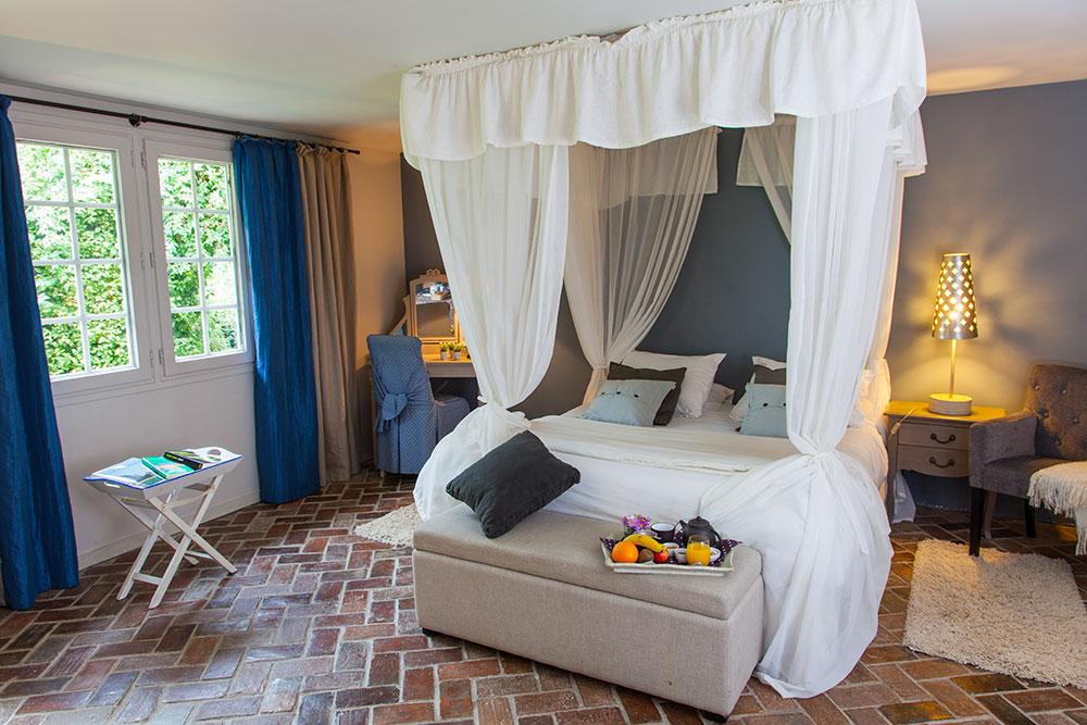 Grand lit double à baldaquin dans la chambre lodge marine et espace bureau pour un weekend ou un séjour romantique de détente et de bien-être