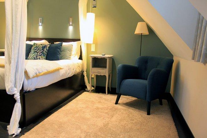 superieur-duplex-chambre-hotel-coussin-dessus-lit-baldaquin-fauteuil-bleu